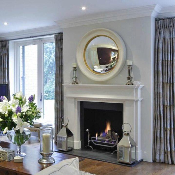 Круглое зеркало в массивной оправе над камином в гостиной
