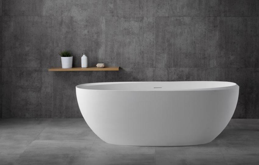 Белая ванна из искусственного камня на фоне серых стен