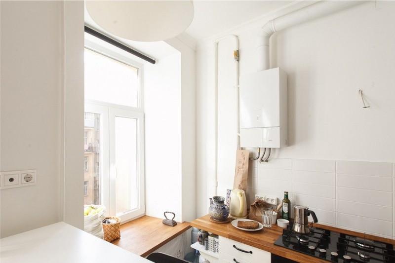 Газовая колонка на белой стене кухни
