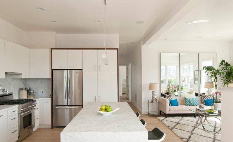 Кухонный остров белого цвета в кухне-столовой загородного дома