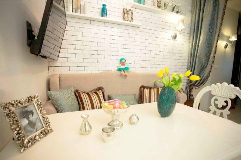 Обеденный стол перед кухонным диваном