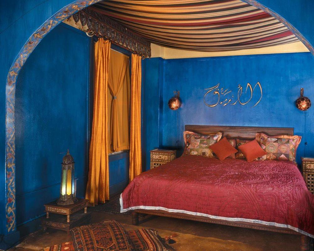 Синие стены спальни с дорогим текстилем