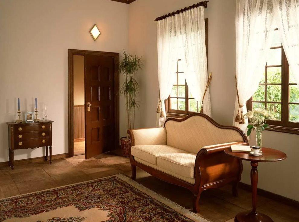 Кушетка на деревянном каркасе в комнате со светлыми шторами