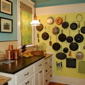Много сковородок на стене кухни