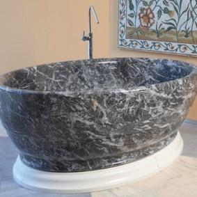 Каменная ванна серого цвета на белом пьедестале