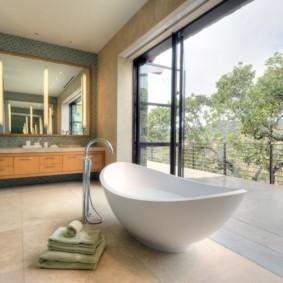 Белая ванна в комнате с панорамными окнами