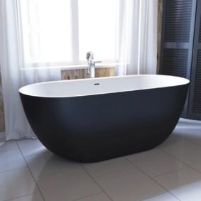 Черная ванна на белом полу