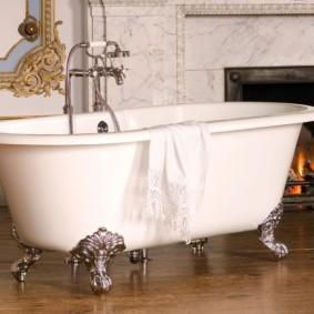 Белая ванна в комнате с камином