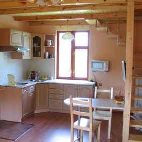 Сельская кухня под лестницей деревянного дома