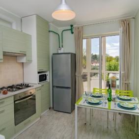 Двухкамерный холодильник около кухонного окна