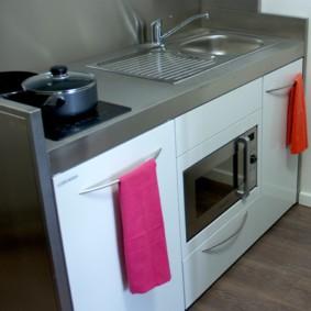 Розовое полотенце на рукоятке посудомоечной машинки