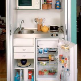 Маленький холодильник под кухонной столешницей