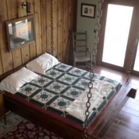 Широкая кровать на цепях в спальне частного дома