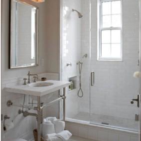Корзинка с белыми полотенцами на полу ванной
