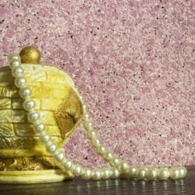 Ожерелье из искусственного жемчуга на фоне стены с жидкими обоями