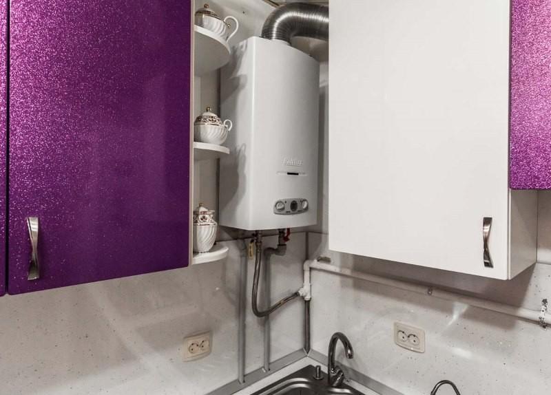 Газовая колонка в углу кухни между шкафами гарнитура
