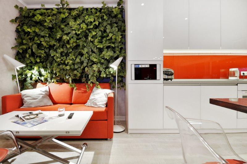 Красный диван в кухне-гостиной с красным фартуком