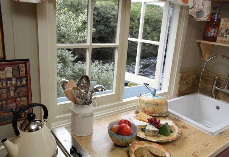 Кухонная мойка перед окном с деревянной рамой