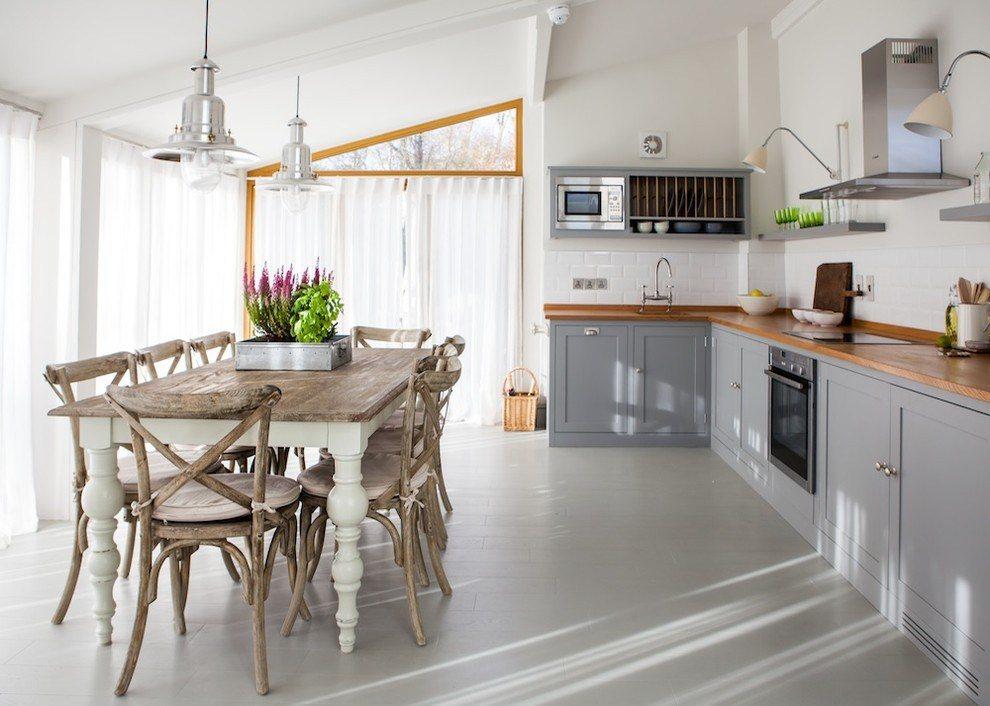 Белые стены в кухне-гостиной с деревянным столом