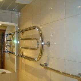 Полотенцесушитель водяного типа на стене с керамической отделкой