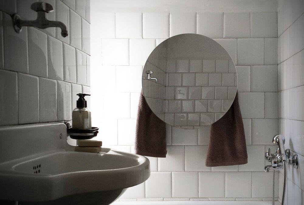 Полотенцесушитель с зеркалом на стене ванной комнаты