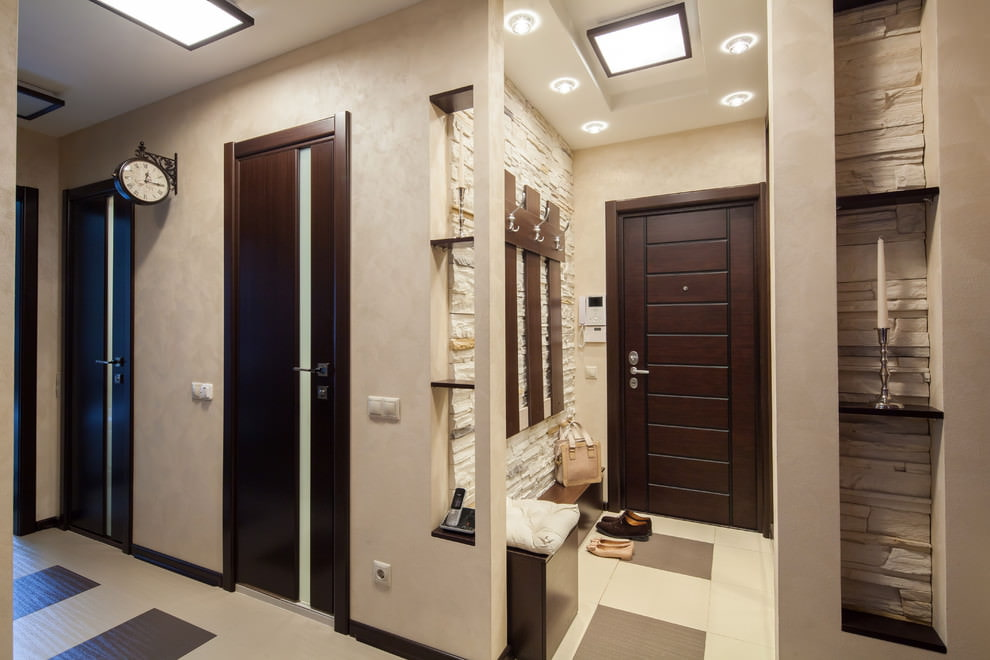 Светлый коридор квартиры с входной дверью темного цвета
