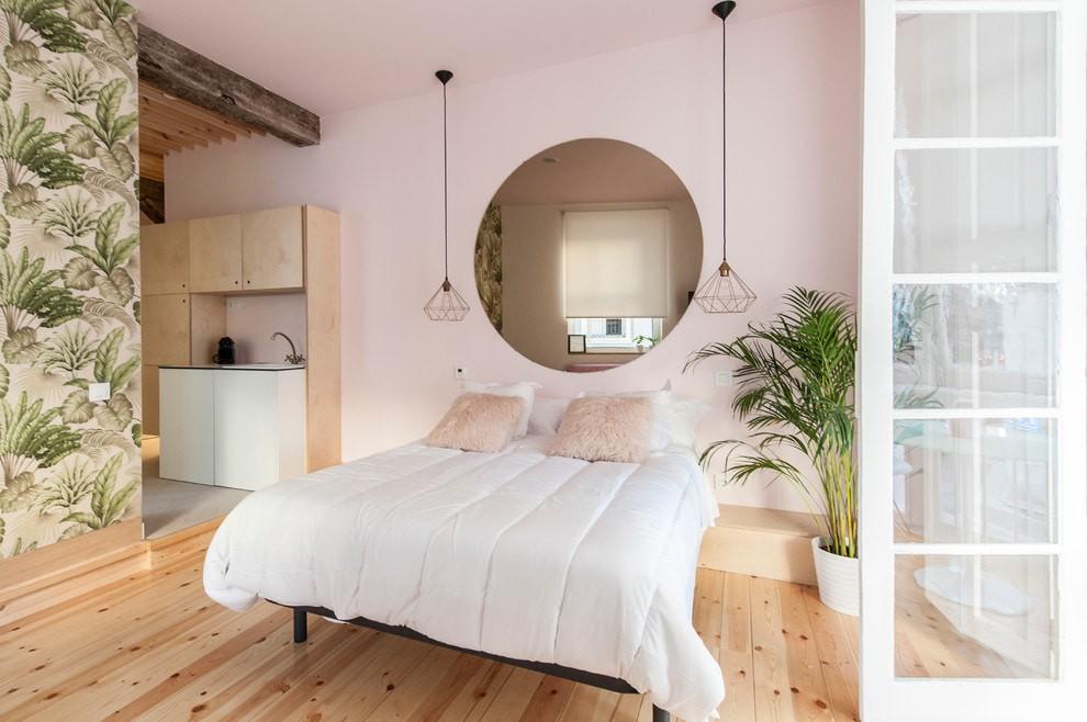 Белое покрывало на кровати в спальне с розовыми стенами