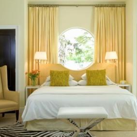 спальня с кроватью у окна в светлых тонах