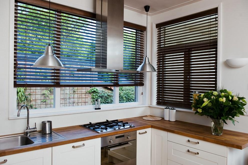 Темны горизонтальные жалюзи на кухонных окнах