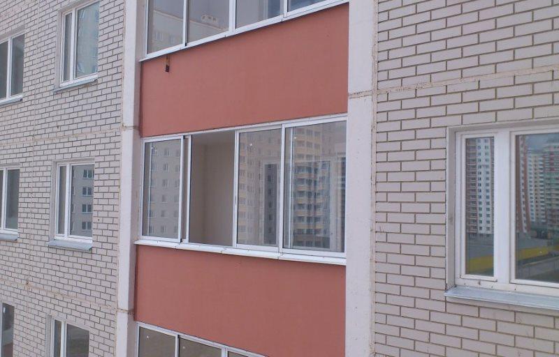 Застекленная лоджии на фасаде кирпичной многоэтажки