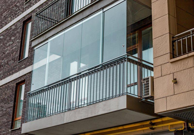 Застекленный балкон на фасаде многоэтажного дома