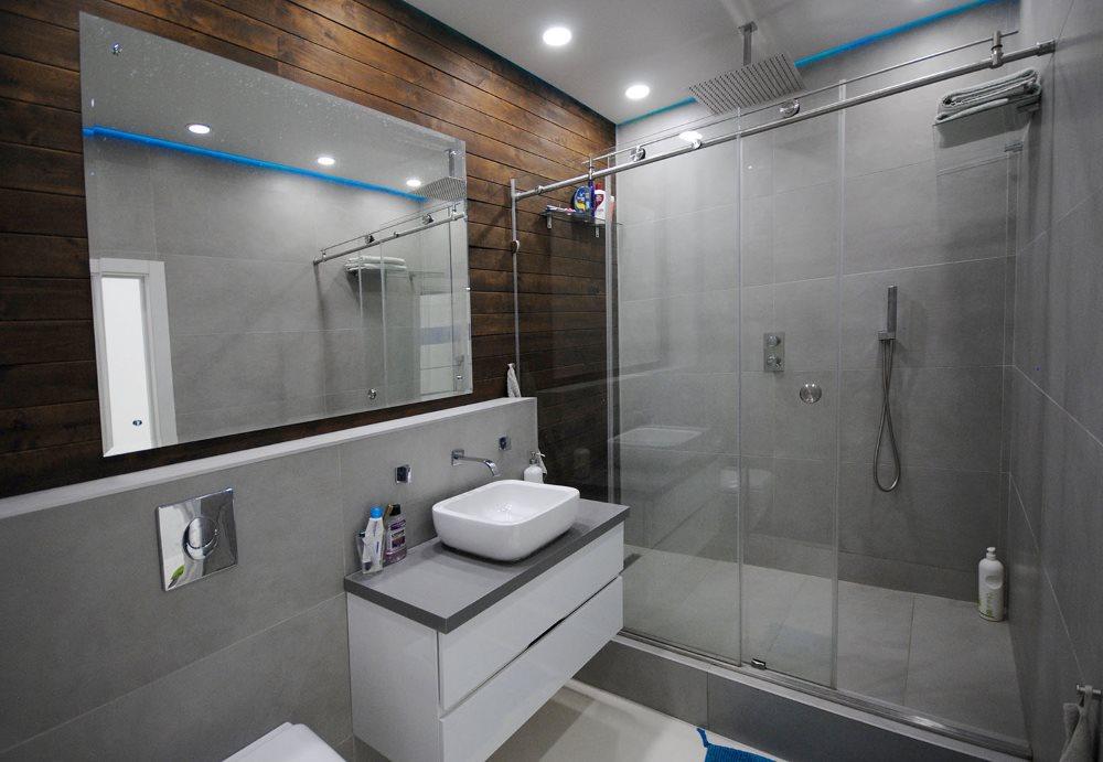 Большое зеркало на стене ванной с душем