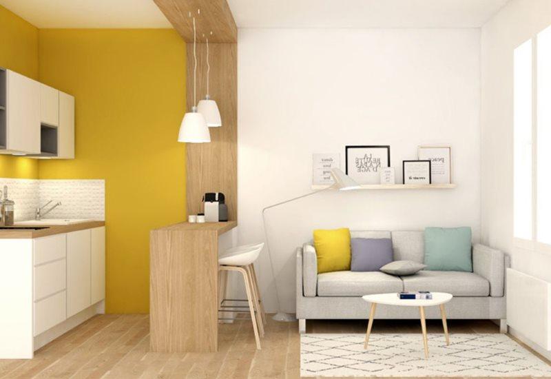 Прямой диван на кухне с желтой стеной