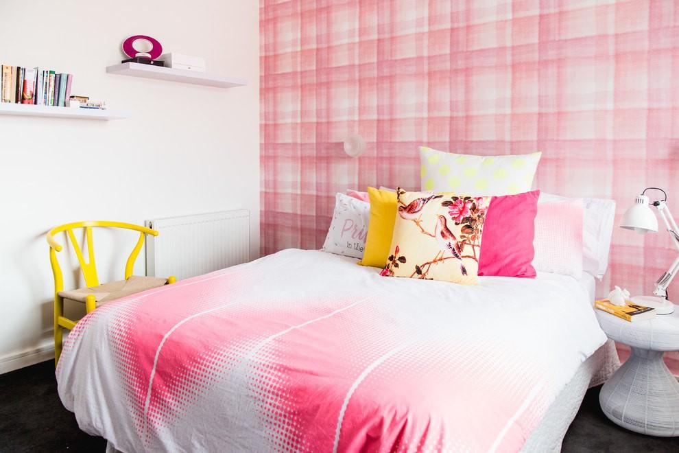 Желтый стул возле кровати с бело-розовым покрывалом