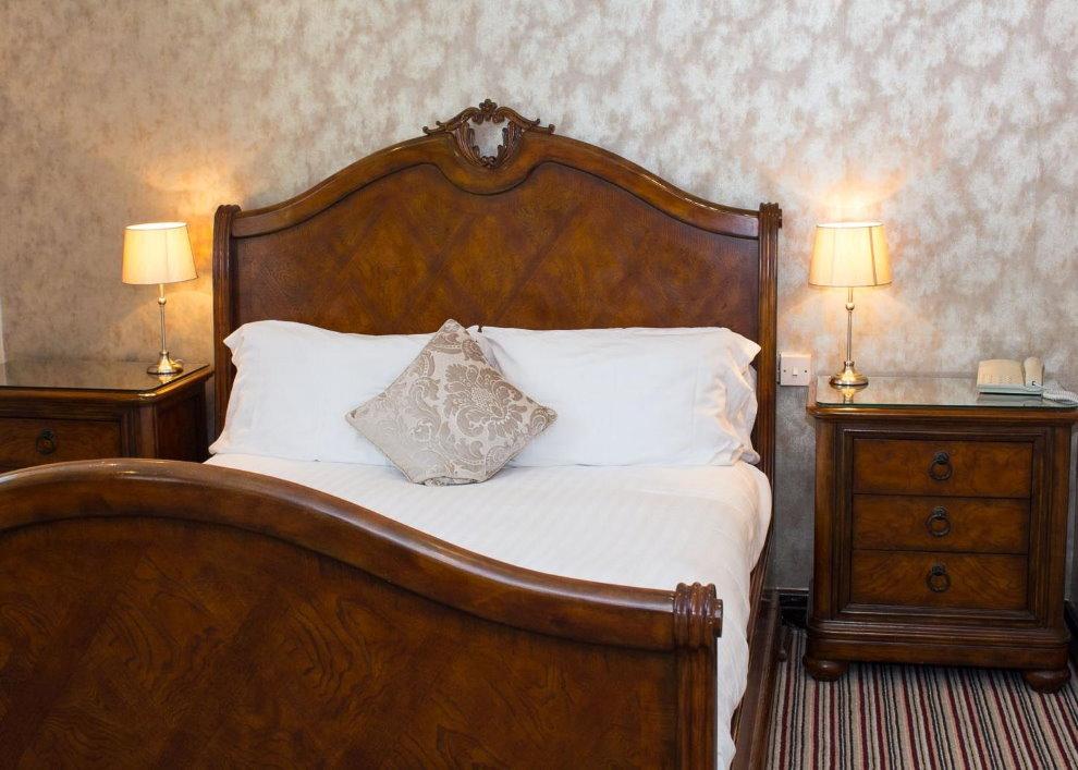 Деревянная кровать в спальне английского стиля