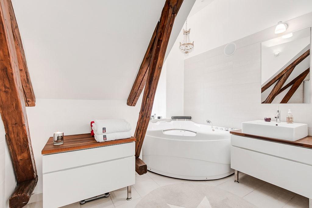 Деревянные балки на фоне белого скошенного потолка