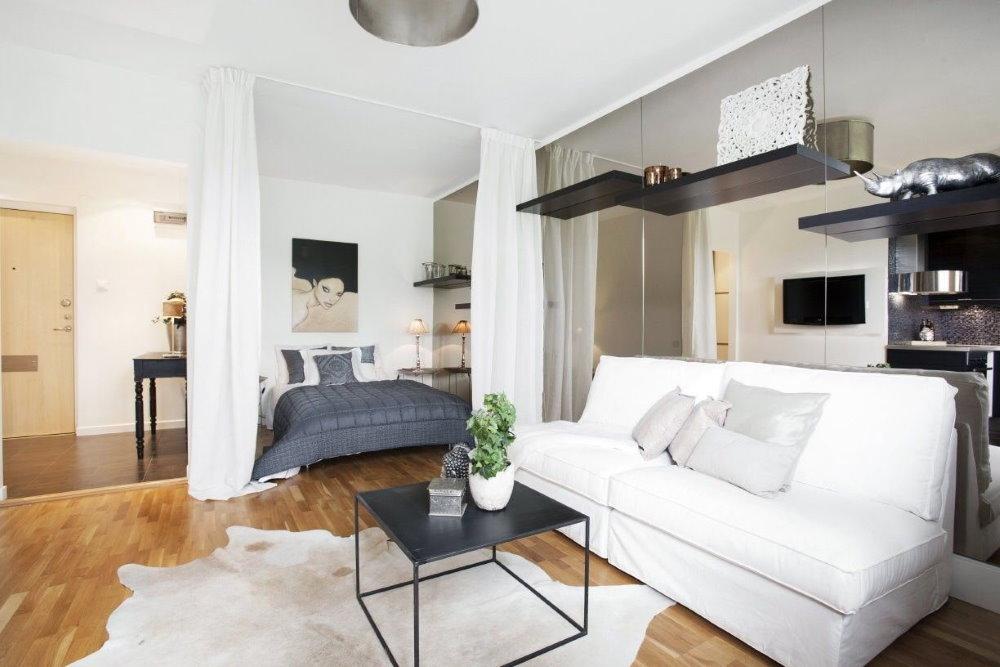 Белые занавески в спальной зоне квартиры-студии