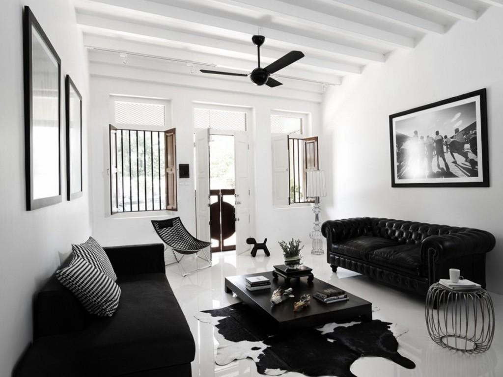 Белые балки на потолке гостиной с черным диваном