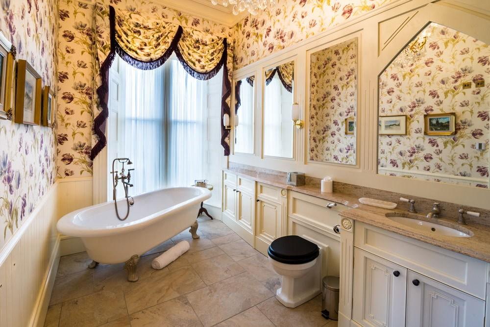 Белая ванна на ножках перед окном в частном доме
