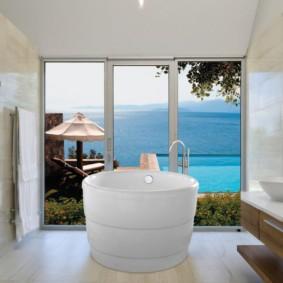 Круглая ванна перед большим окном