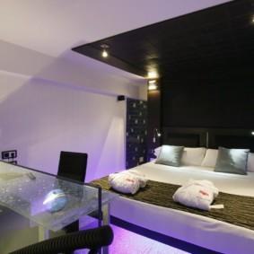 Двухспальная кровать в комнате с черной стеной