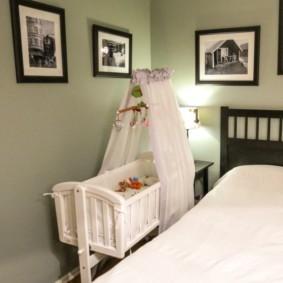 Детская колыбелька рядом с кроватью родителей