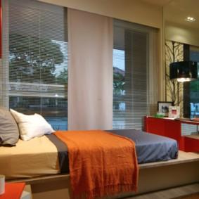 Узкая кровать перед большим окном