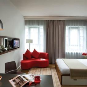 Красный диванчик в гостиной с двумя окнами