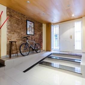 Велосипед около кирпичной стены в прихожей