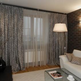 Белый диван возле стены с обоями под кирпич