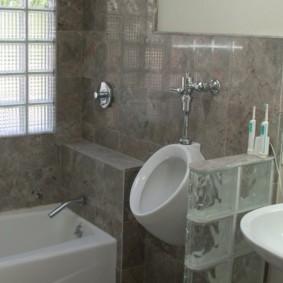 Серая плитка на стене совмещенной ванной