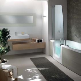 Серый коврик на полу ванной комнаты