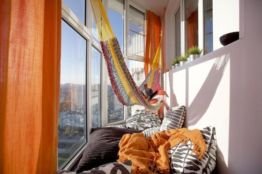 Множество подушек на полу балкона с панорамным остеклением