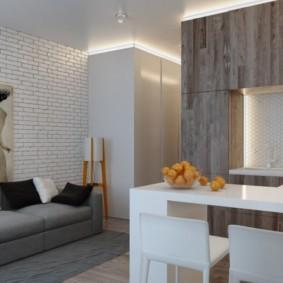Серый диван возле кирпичной стены